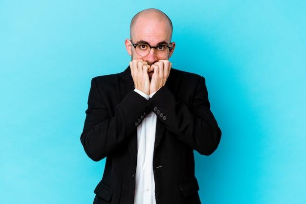 若いビジネス白人ハゲ男は、青い背景に爪を噛んで孤立し、神経質で非常に心配しています。