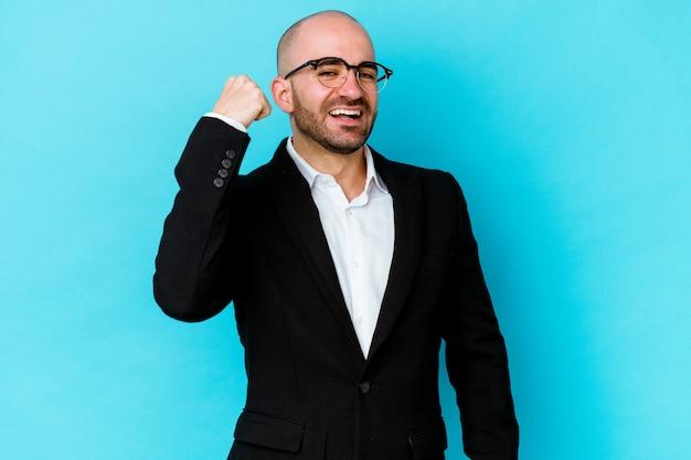 평온한 및 흥분 응원 파란색 배경에 고립 된 젊은 비즈니스 백인 대머리 남자. 승리 개념.