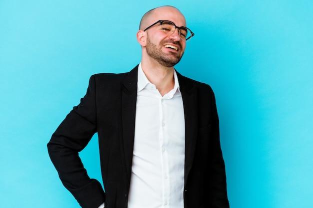 Молодой деловой кавказский лысый человек, изолированные на синем фоне, уверенно держит руки на бедрах.