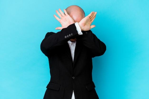 若いビジネス白人ハゲ男は、2つの腕を交差させたまま、青い背景で隔離、概念を否定します。