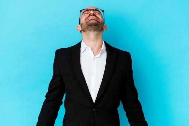 파란색 배경에 고립 된 젊은 비즈니스 백인 대머리 남자 편안하고 행복 웃음, 목 뻗어 보여주는 이빨.