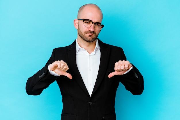 嫌いなジェスチャーを示す青い背景に分離された若いビジネス白人ハゲ男、親指を下に。不一致の概念。