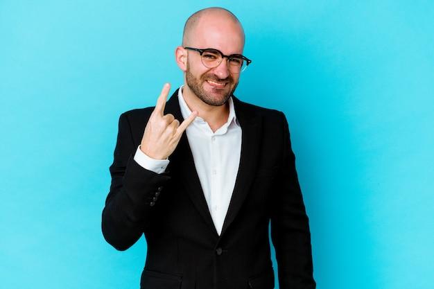 指でロックジェスチャーを示す青い背景に分離された若いビジネス白人ハゲ男