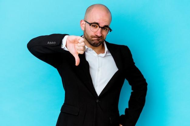 Молодой бизнес кавказский лысый человек, изолированные на синем фоне, показывая большой палец вниз, концепция разочарования.