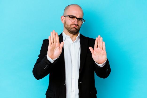 青の背景に孤立した若いビジネス白人ハゲ男は、一時停止の標識を示している手を伸ばして立って、あなたを妨げています。