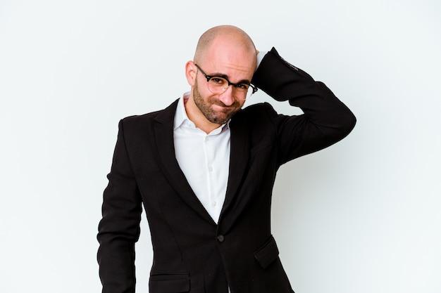 앉아있는 생활 방식으로 인해 목 통증을 겪고 파란색 배경에 고립 된 젊은 비즈니스 백인 대머리 남자.