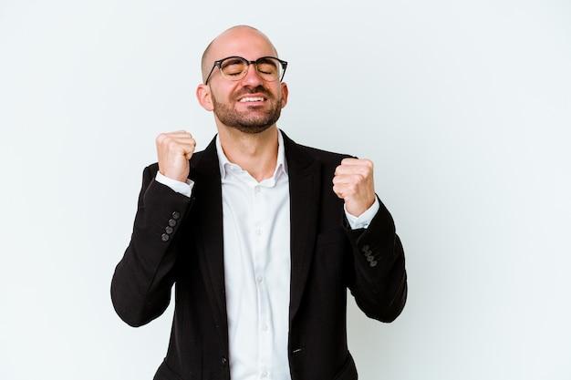 勝利、情熱と熱意、幸せな表現を祝う青い壁に孤立した若いビジネス白人ハゲ男