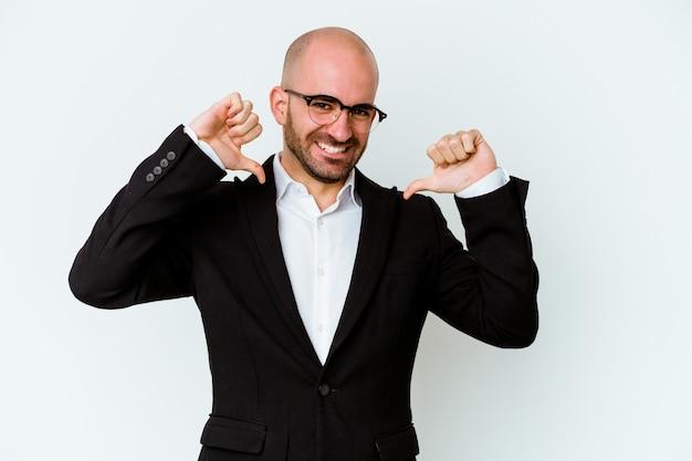 青い壁に隔離された若いビジネス白人ハゲ男は誇りと自信を持って感じます、従うべき例