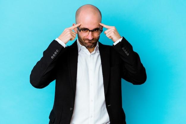 Молодой деловой кавказский лысый мужчина изолирован на синей стене, сосредоточившись на задаче, держа указательные пальцы, указывая головой