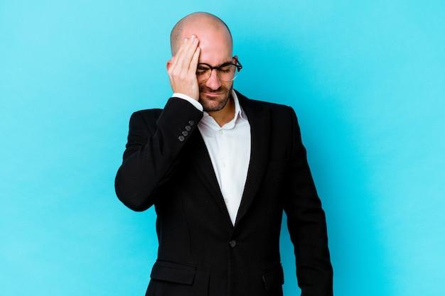 Молодой деловой кавказский лысый мужчина изолирован на синей стене с головной болью, касаясь передней части лица