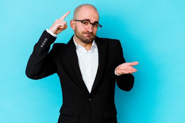젊은 비즈니스 백인 대머리 남자를 손에 제품을 보여주는 파란색 벽에 고립.