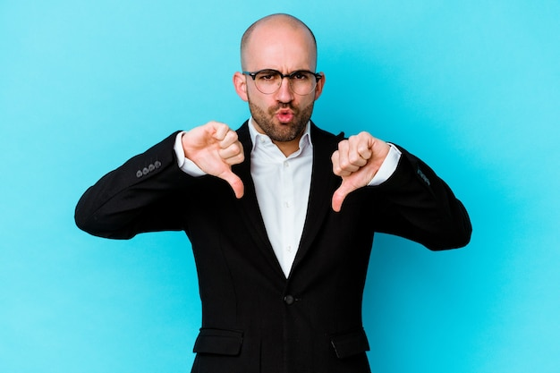 Молодой деловой кавказский лысый мужчина изолирован на синей стене, показывая большой палец вниз и выражая неприязнь.