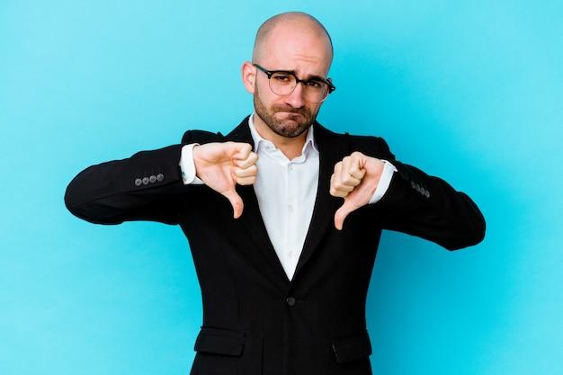 Молодой деловой кавказский лысый мужчина изолирован на синей стене, показывая большой палец вниз