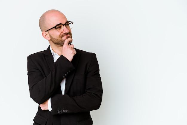 Молодой деловой кавказский лысый мужчина на белом фоне смотрит в сторону с сомнительным и скептическим выражением лица.