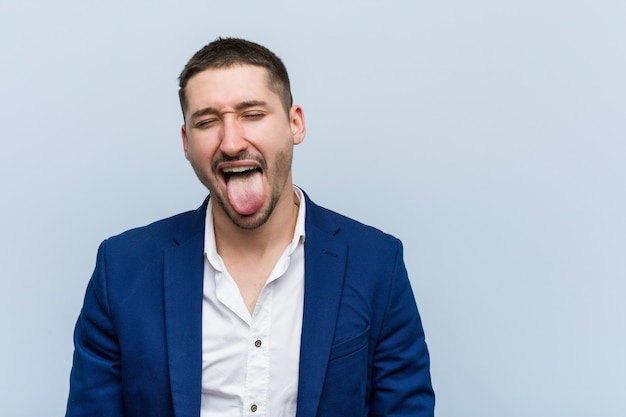 Young business caucasian man funny and friendly sticking out him tongue.
