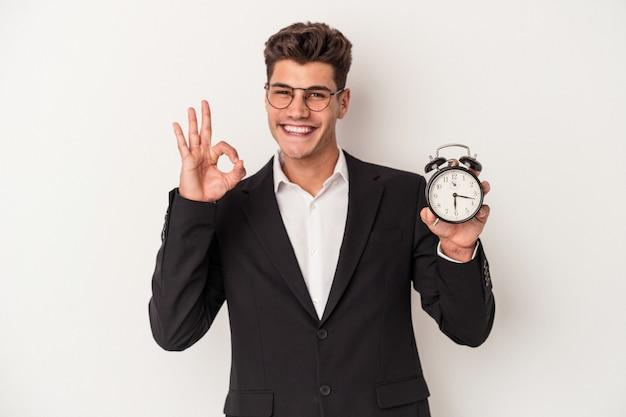 白い背景で隔離の目覚まし時計を保持している若いビジネス白人男性は、大丈夫なジェスチャーを示す陽気で自信を持っています。