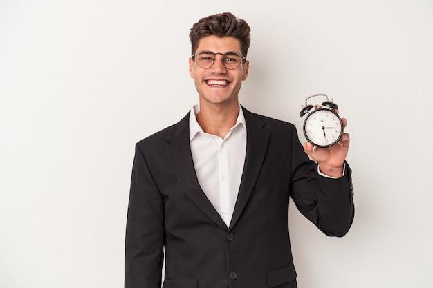 幸せ、笑顔、陽気な白い背景で隔離の目覚まし時計を保持している若いビジネス白人男性。