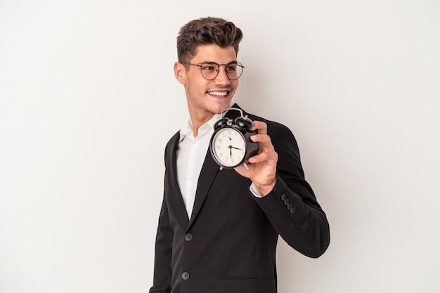 白い背景で隔離の目覚まし時計を保持している若いビジネス白人男性は、笑顔、陽気で楽しい脇に見えます。
