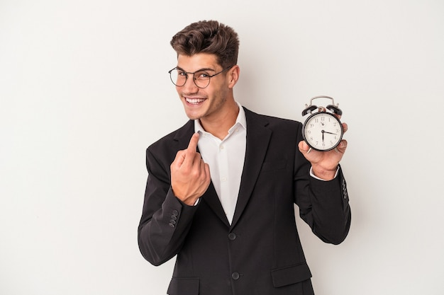 誘うようにあなたに指で指している白い背景で隔離の目覚まし時計を保持している若いビジネス白人男性が近づいています。