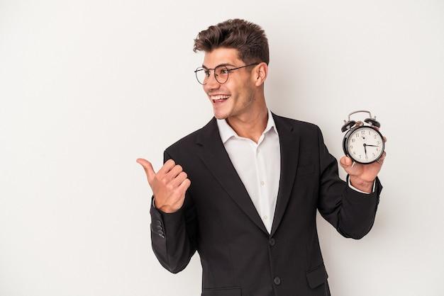 目覚まし時計を保持している若いビジネス白人男性は、親指の指を離れて、笑ってのんびりと白い背景のポイントに分離されました。