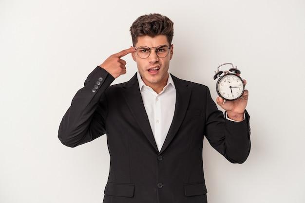 人差し指で失望のジェスチャーを示す白い背景で隔離の目覚まし時計を保持している若いビジネス白人男性。