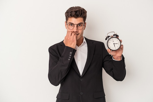 Young business caucasian man holding alarm clock isolated on white background biting fingernails, nervous and very anxious.