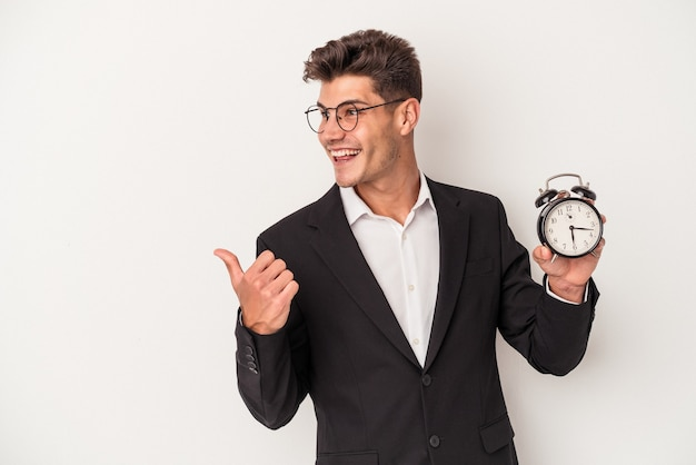 Young business caucasian man holding alarm clock isolated on white background points with thumb finger away, laughing and carefree.