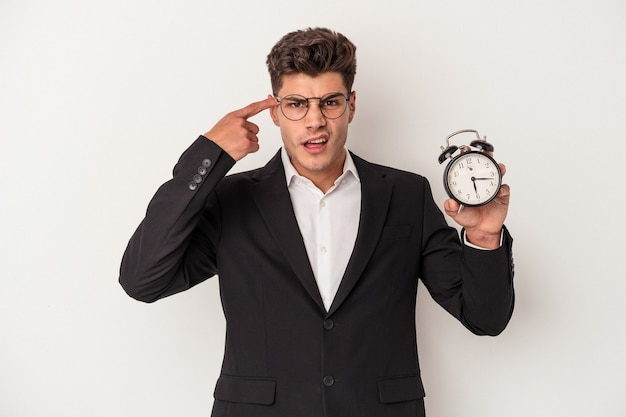 Young business caucasian man holding alarm clock isolated on white background showing a disappointment gesture with forefinger.