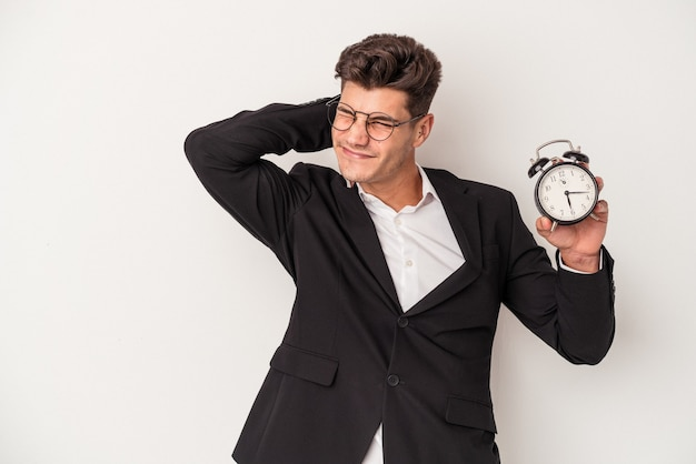 Young business caucasian man holding alarm clock isolated on white background touching back of head, thinking and making a choice.