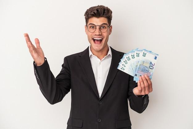 白い背景に分離された紙幣を保持している若いビジネス白人男性は、嬉しい驚きを受け取り、興奮し、手を上げます。