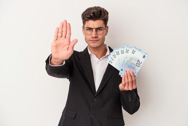 白い背景で隔離の紙幣を保持している若いビジネス白人男性は、一時停止の標識を示している手を伸ばして立って、あなたを妨げています。