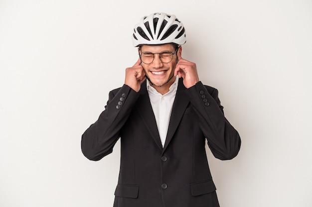 手で耳を覆う白い背景で隔離の自転車のヘルメットを保持している若いビジネス白人男性。