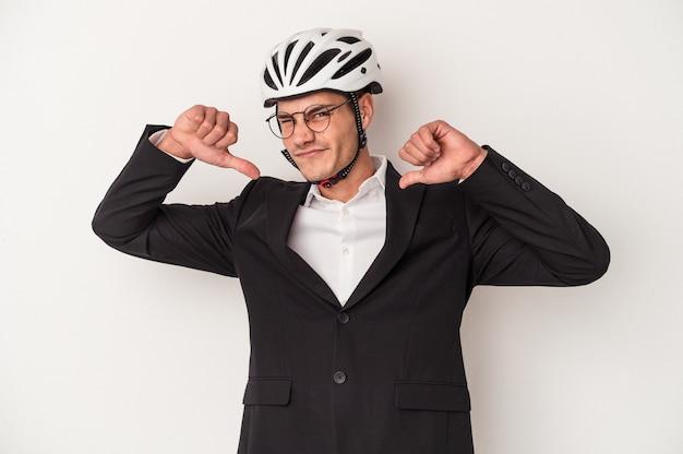 白い背景で隔離の自転車のヘルメットを保持している若いビジネス白人男性は、誇りと自信を持って、従うべき例を感じます。