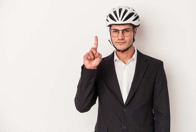 指でナンバーワンを示す白い背景で隔離の自転車のヘルメットを保持している若いビジネス白人男性。