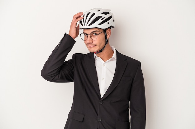 Young business caucasian man holding bike helmet isolated on white background being shocked, she has remembered important meeting.