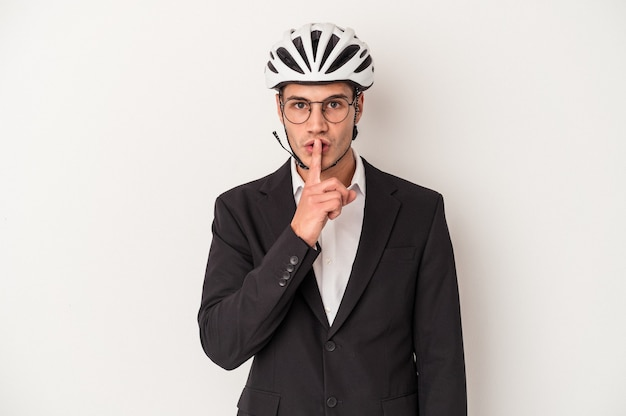 Young business caucasian man holding bike helmet isolated on white background keeping a secret or asking for silence.