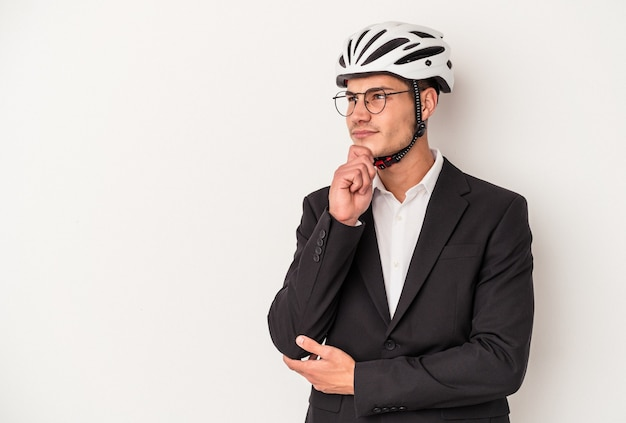 Young business caucasian man holding bike helmet isolated on white background looking sideways with doubtful and skeptical expression.