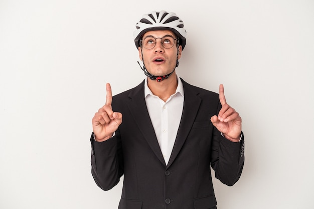 Young business caucasian man holding bike helmet isolated on white background pointing upside with opened mouth.