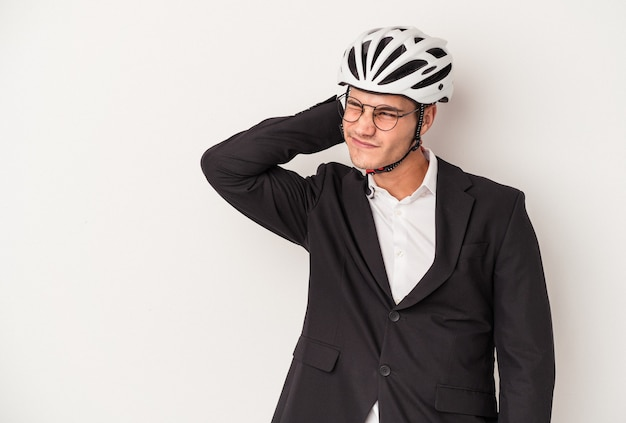 Young business caucasian man holding bike helmet isolated on white background touching back of head, thinking and making a choice.