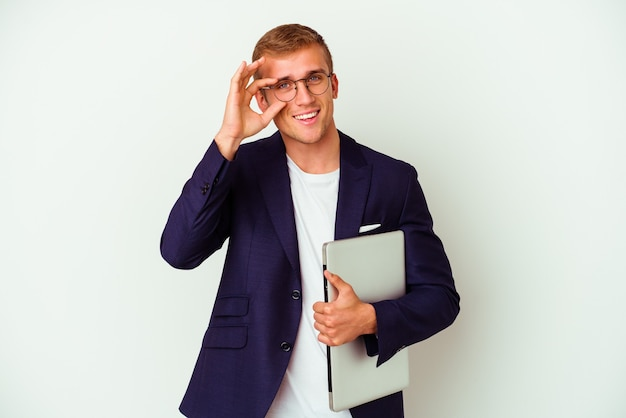 Young business caucasian man holding a laptop isolated on white excited keeping ok gesture on eye.