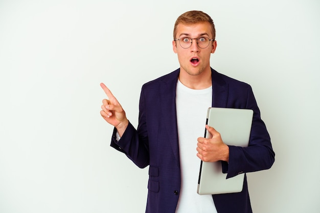 Young business caucasian man holding a laptop isolated on white pointing to the side