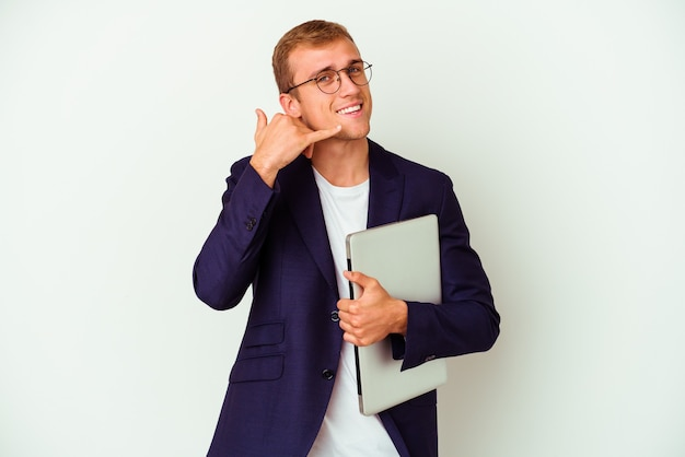 Young business caucasian man holding a laptop isolated on white showing a mobile phone call gesture with fingers.