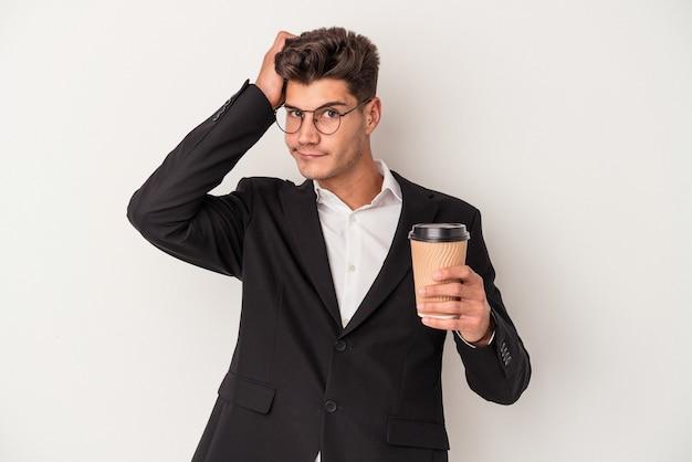 ショックを受けている白い背景で隔離のコーヒーをテイクアウトを保持している若いビジネス白人男性、彼女は重要な会議を思い出しました。