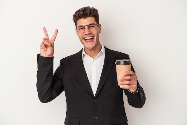 保持している若いビジネス白人男性は、指で平和のシンボルを示して楽しくてのんき白い背景で隔離のコーヒーをテイクアウトします。