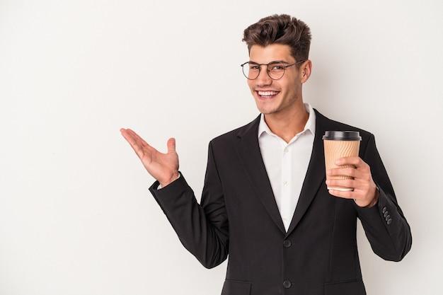 手のひらにコピースペースを示し、腰に別の手を保持している白い背景で隔離のコーヒーをテイクアウトを保持している若いビジネス白人男性。