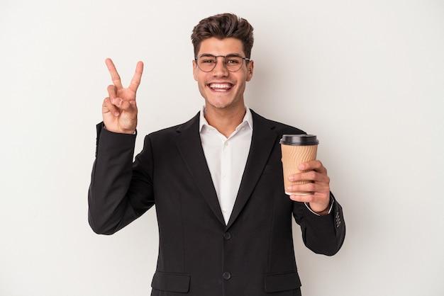 保持している若いビジネス白人男性は、指で2番目を示す白い背景で隔離のコーヒーをテイクアウトします。