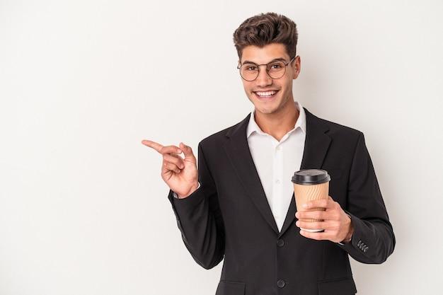 保持している若いビジネス白人男性は、笑顔と脇を指して、空白のスペースで何かを示して、白い背景で隔離のコーヒーをテイクアウトします。