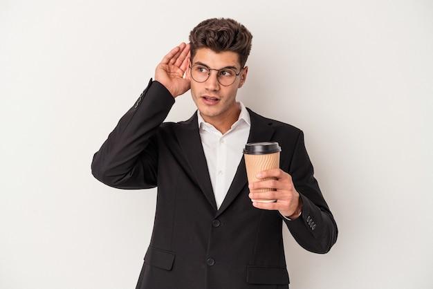 ゴシップを聴こうとしている白い背景で隔離のコーヒーをテイクアウトを保持している若いビジネス白人男性。
