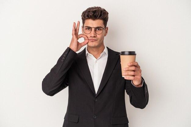 保持している若いビジネス白人男性は、秘密を保持している唇に指で白い背景で隔離のコーヒーをテイクアウトします。