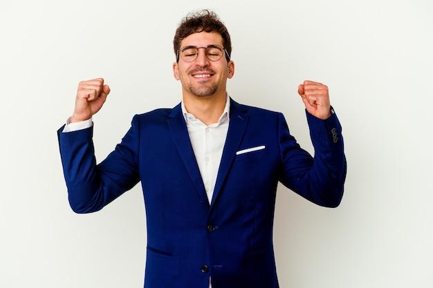 勝利、情熱と熱意、幸せな表現を祝う白い背景で隔離の若いビジネス白人男性。